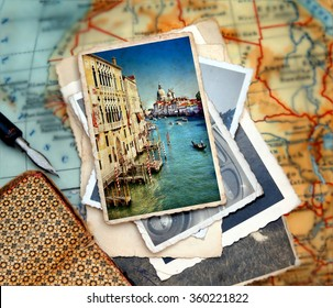 Beautiful vacation photograph from  from the Grand Canal of Venice with the famous landmark cathedral Santa Maria della Salute laying on a desk with several images and a journal with pencil