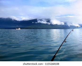 Beautiful Valdez Bay in the early morning provides peaceful fishing.  Clouds hang low over the Chugach Mountains, and a ship glides over the water.