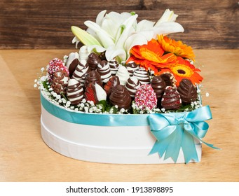 Beautiful Valentine's Gift; a heart-shaped box filled with chocolate-covered strawberries accompanied by flowers.