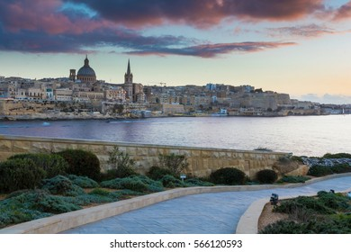 Beautiful Valletta skyline under a vibrant colorful golden sunset, seen across the water from the paths around Tigne Point, Sliema, Valletta is the capital city of Malta, Europe