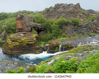 Beautiful Valley Gjain with colorful lava rocks, green vegetation and blue water stream cascade in south Iceland