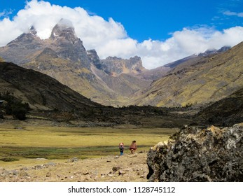 Beautiful valley in the peruvian Andes, with view of high peaks with glaciers and some locals in colorful clothes. Photo taken on the Lares Trek near Machu Picchu,