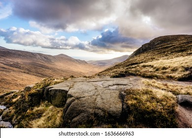 Beautiful valley with river in Mourn Mountains at autumn colours. Dramatic cloudy sky. Highest and most dramatic mountain range in Northern Ireland.