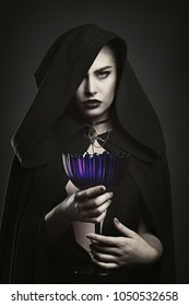 Beautiful vampire holding a cup. Blood ritual