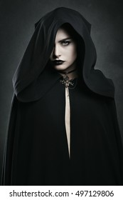 Beautiful vampire woman with black cloak . Halloween and horror