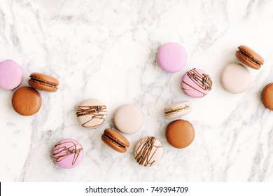 Beautiful variety of macaroons on marble background. Stylish arrangement sweet. Flat lay, top view.