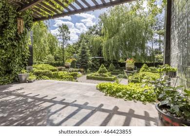 Beautiful vast garden in Japanese style seen from a shaded veranda