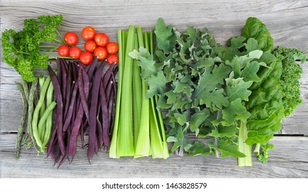 Beautiful vegetable harvest arrangement on wood background. From left to right: parsley, dragon tongue beans, green beans, purple beans, cherry tomatoes, celery, Russian kale, Swiss chard, green kale.