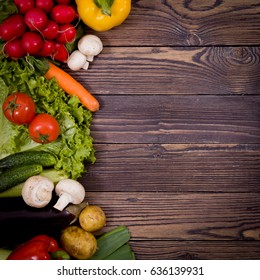 Beautiful vegetables and fruits are lined at the top on a wooden background. In the middle, there is room for text or logo insertion. Foul for advertising. Vegetarian dietary box. Healthy lifestyle