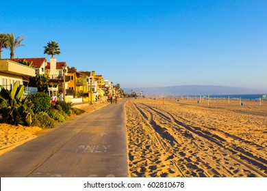 Beautiful Venice beach area in Los Angeles with a pedestrian walk during orange sunset. Empty beach, golden sand, no people.