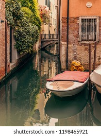 Beautiful Venice canal with brick wall, bridge glimpse and resting boats in Summer