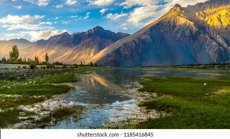 Beautiful vertical landscape with mountains in Himalayas reflection in lake water having blue sky  of Nubra valley in Leh, Ladakh which is a paradise for bike travel in India