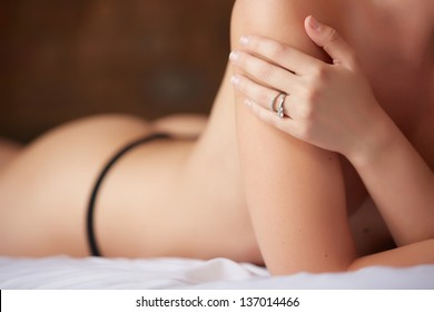 Beautiful and very sexy young adult caucasian woman in Black lingerie with blonde hair and blue eyes, in a bedroom setting with typical boudoir poses