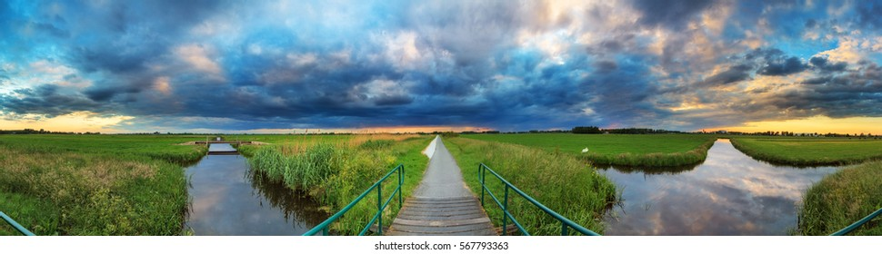 Beautiful vibrant 360 degree panorama of a polder landscape in the Netherlands with a typical dutch cloudy sky in spring