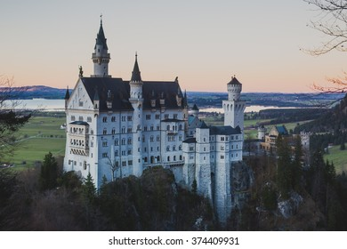 Beautiful vibrant autumn view of famous Neuschwanstein Castle, the 19th century Romanesque Revival palace with mountain landscape near Fussen and Munich, southwest Bavaria, Germany, on dawn or dusk
