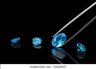 Beautiful vibrant big blue topazs gemstone, one is being held by a tweezers on reflective black background