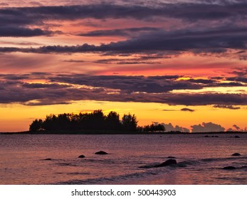 Beautiful vibrant ocean sunset with small island and clouds.