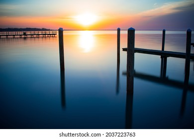 Beautiful and vibrant sunrise over Lake St. Clair from Walter Mary Burke Park Pier. Blue, orange, yellow, and purple hues along with a clear reflection. Pier located in New Baltimore, MI.