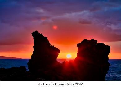 Beautiful and vibrant sunset through lava rock at Wailea Beach in Wailea, Maui, Hawaii