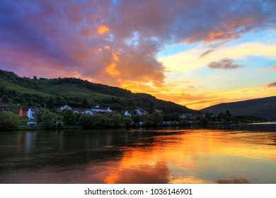 Beautiful vibrant sunset view of the river Moselle at the small wine growing town Zell (an der Mosel) with hills full of grape vines
