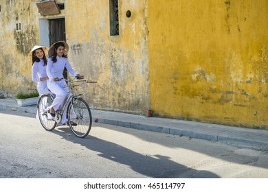 Beautiful Vietnam ladies ride a bicycle who wearing Ao dai. It's a vietnamese national costume. Many people hope to preserved vietnamese culture. You can see from many city  Ex. hue, hoi an and danang