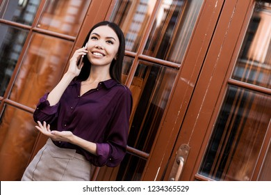 Beautiful Vietnamese business woman calling on the phone when walking outdoors, gping to coworking, tallking about project with partners. Professional, leader, succesfull woman.