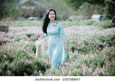 Beautiful Vietnamese girl in Ao dai, traditional dress in a garden of flower