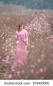 Beautiful Vietnamese girl in traditional dress  and smiling in peach flower garden