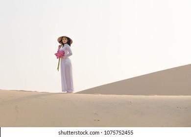 Beautiful Vietnamese holding Pink Lotus in White Sand dune desert, Muine, Vietnam