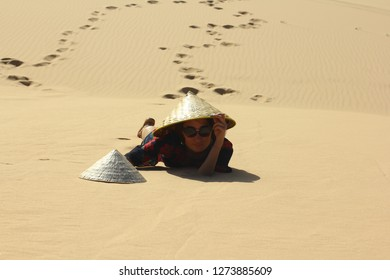 Beautiful vietnamese lady in long dress on the white sand dunes with vietnamese hat.