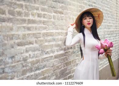 Beautiful vietnamese woman in white Ao Dai traditional dress of Vietnam, Ho Chi Minh city Vietnam