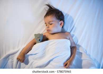 Beautiful view from above of adorable baby sleeping in white bed at night. Little toddler   taking a nap in dark room with lamplight and toy bear. Bed time for kids. Bedroom and nursery interior.