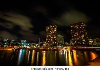 Beautiful view of Ala Wai Harbor, the largest yacht harbor of Hawaii at night. Honolulu Harbor skyline reflecting in the water. Oahu in Hawaii, United States.