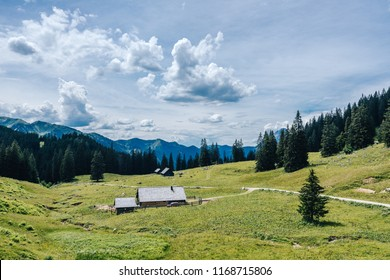Beautiful view of an Alm hutte in Gesause, Austria. Summer alpine landscape with pastures, huts and green grass, blue sky and peaks in the background. Almrundweg  and the Hochtor summit.