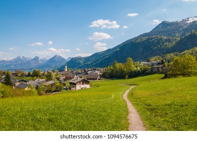 Beautiful view of alpine austrian town St.Gilgen on Wolfgangsee lake, walking path through a green meadow and mountains on the background. Salzburger land, Austria