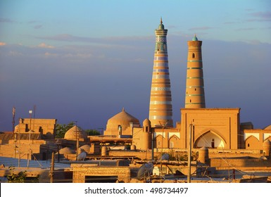 Beautiful view of ancient Itchan Kala fortress and Mosque in the light of evening sun, background of cloudy blue sky in Historic Center of Khiva (UNESCO World Heritage Site), Uzbekistan, Central Asia