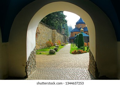 Beautiful view from arch in ancient Manyava Skete. Bright day seen in arch of religious place. Spiritual place in Western Ukraine