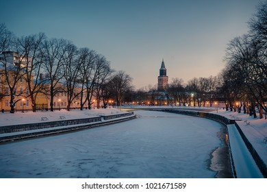 Beautiful view of Aura river at clear winter morning with street lights on and Turku Cathedral in the background