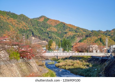 The beautiful view of Autumn Trees and Fall colors Mountain in background with japanese bridge over Araki blue River flows through furukawa old town Hida-Furukawa, Gifu, Chubu, Japan