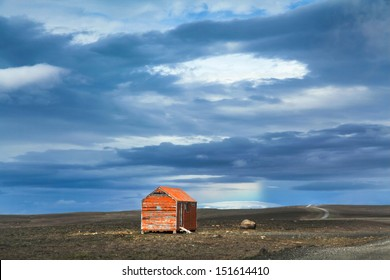 Beautiful view of barren landscape with old red snowstorm shelter at Kjolur highland road, Iceland