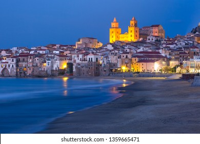 Beautiful view of the beach, Cefalu Cathedral and old town of coastal city Cefalu during evening blue hour, Sicily, Italy