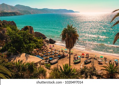 Beautiful view of a beach in Nerja, Costa del Sol in Andalucia with cristal water from a balcony. With a giant palm tree and lots of people having fun in the sand