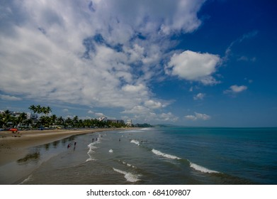 Beautiful view of the beach with sand, and buildings behind in a beautiful day in with sunny weather in a blue sky in Same, Ecuador