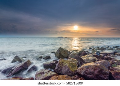 a beautiful view of beach side, sunset or sunrise moment, waves from sea and rocks. Nature landscape photo