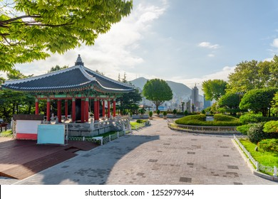 Beautiful view of bell pavilion of traditional Korean architecture at Yongdusan Park in Busan, South Korea. The city is visible in background. Wonderful summer sunny cityscape.
