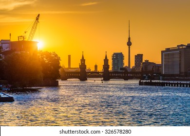 Beautiful view of Berlin skyline with famous TV tower and Oberbaum Bridge at river Spree in golden evening light at sunset, Berlin Friedrichshain-Kreuzberg, Germany