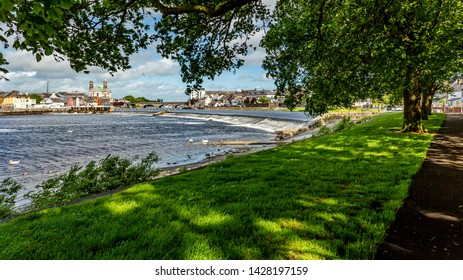 Beautiful view between the branches of the trees of the Shannon River with the town of Athlone in the background, wonderful sunny day in the county of Westmeath, Ireland