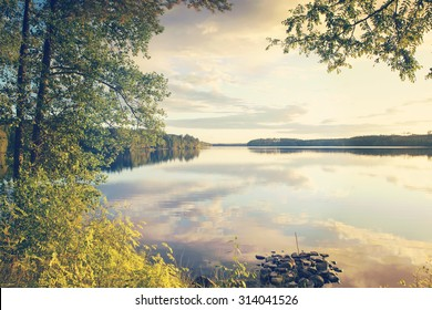 A beautiful view by the lake during sunset on a summer evening. Some clouds are reflecting from the still water. Image taken through tree branches. Also a vintage effect is applied to the image.