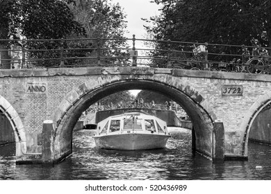 Beautiful view of a canal boat under a bridge at the famous UNESCO world heritage canals of Amsterdam, the Netherlands, in black and white.