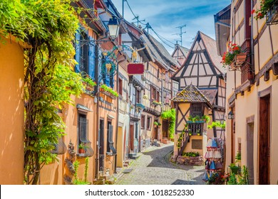 Beautiful view of charming street scene with colorful houses in the historic town of Eguisheim on an idyllic sunny day with blue sky and clouds in summer, Alsace, France
